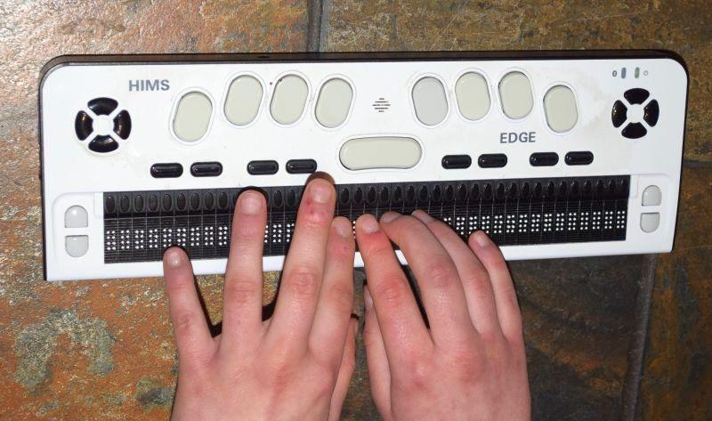 Man sieht meine Hände auf der Braillezeile, die gerade einen Text lesen.